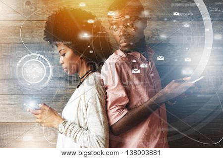 Visual Effects. Young African Couple Standing Back-to-back, Holding Mobile Phones. Jealous Possessiv