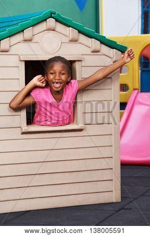 Happy african child cheering in a playhouse in kindergarten
