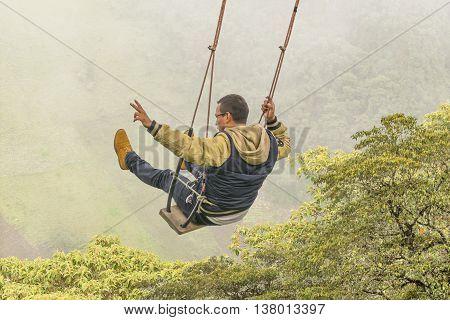 Young Man Swinging At Casa Del Arbol, Banos Ecuador