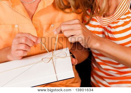 Two women � mother and daughter � sitting on a couch; the daughter has given her mother a gift
