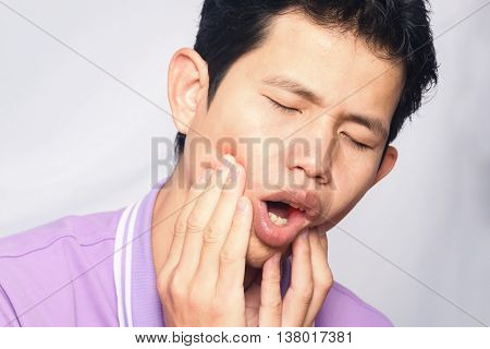 man have  toothache on white background, symptoms of toothaches typically involve some kind of ache or pain in the jaws or gums