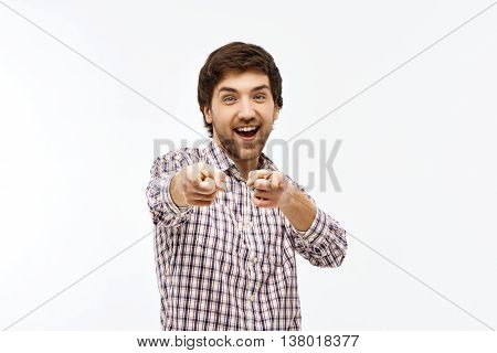 Close-up portrait of handsome smiling young blue-eyed dark-haired man wearing casual plaid shirt looking at camera, pointing forward with fingers. Isolated on white background.
