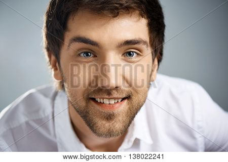 Close up portrait of smiling elegant joyful handsome young businessman in white shirt looking at camera. Studio, isolated on grey background.