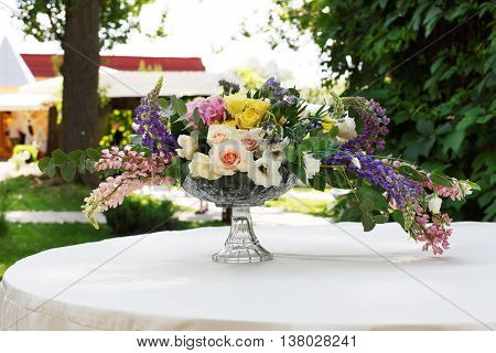 Beautiful flower composition outdoors. Wedding floristic decoration at white round table, bouquet of colorful wildflowers and white roses in glass vase