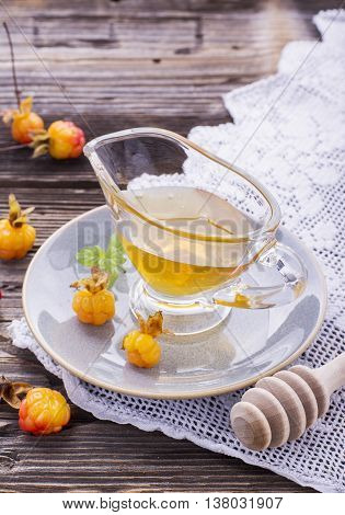 Cloudberry honey in a gravy boat on a saucer with ripe berries arctic cloudberries on a simple wooden background with vintage cloth embroidery