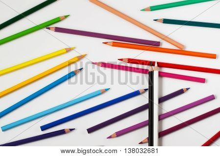 Pair black and white pencils top from assortment of pencils in a variety of colors, on white background