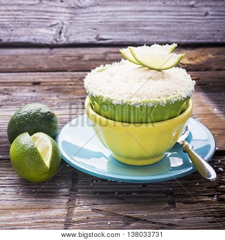 Healthy breakfast snack. Easy homemade coconut cup cupcake with lime zest in portioned bowls on a wooden background
