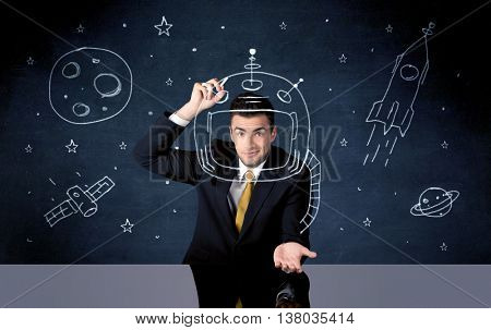 A young happy businessman in elegant suit drawing helmet, satellite and rocket in empty space with a chalk illustration concept