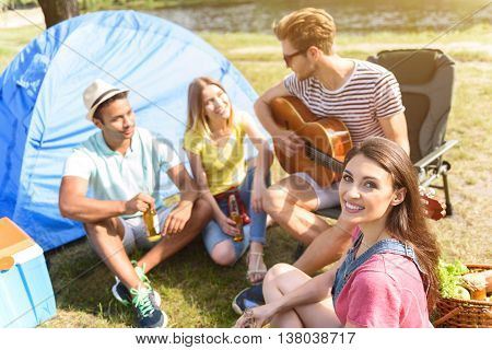 Happy young men and women enjoying nature together. They are singing songs to guitar and smiling. Youngsters are sitting on grass near tent