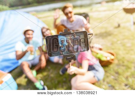 Happy friends are making selfie with stick in nature. They are sitting near tent and laguhing. Focus on mobile phone