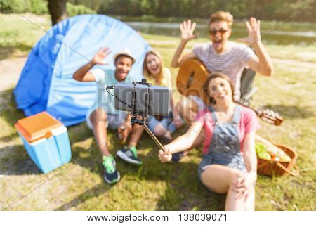 Joyful young friends making selfie and smiling. They are looking at camera and waving arms. Woman is holding stick with mobile phone. Youngsters are sitting on grass near tent
