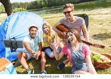Carefree young men and women photographing themselves in the nature. Man is holding stick with smartphone. Woman is sitting and showing peace sign. They are smiling