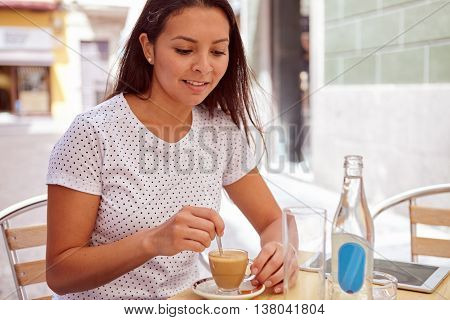 Pretty Young Brunette Stirring Her Coffee