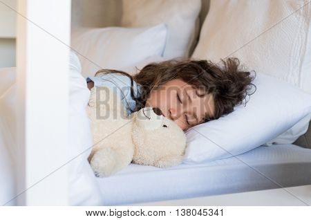 Sweet child sleeping in bed. Little girl sleeping with teddy bear at morning. Cute little girl sleeping peacefully with teddy bear.