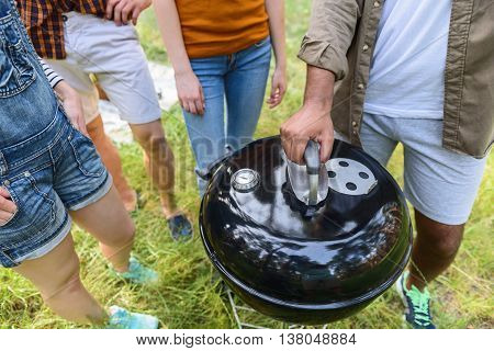 Close up of young men and women waiting for barbecue. Man is standing and opening cover of grill