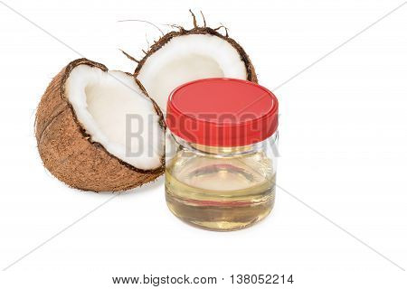 Coconut oil in a glass jar with red cover next to the two halves of coconut isolated on white background