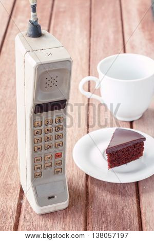 vintage mobile phone with cup of coffee and chocolate cake