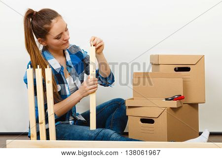 Woman Moving Into Apartment Assembly Furniture.