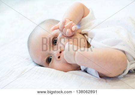 Portrait of a two month infant baby boy teething bites the hand sucking.Close up at infant baby.