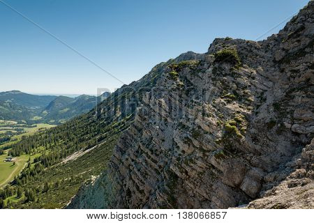 Rocky cliff face near alps showing strata of geologic details under blue sky with copy space poster