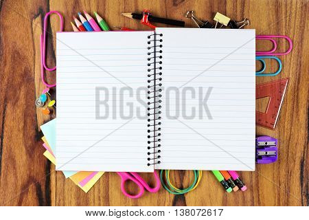 Blank Opened Lined School Notebook With Underlying Frame Of School Supplies Over A Wooden Desk Backg