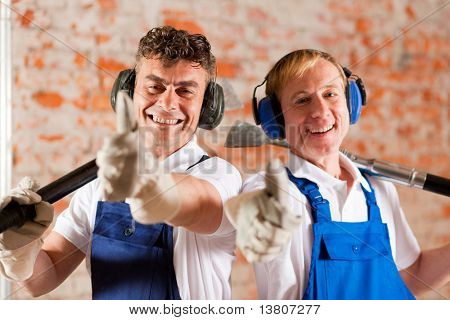 Two construction workers standing in a construction site in front of a brick wall. Their are wearing ear protection and having the thumps up