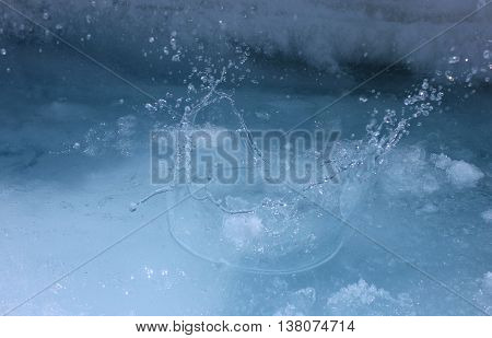 A snowball dropped into clear blue glacier water.