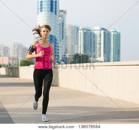 beautiful young woman on a morning jog in the city listening to music in headphones from smartphone fixed in her pocket on the arm