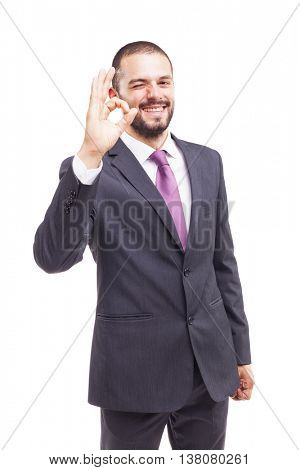 Young business man showing Ok sign, isolated on white background