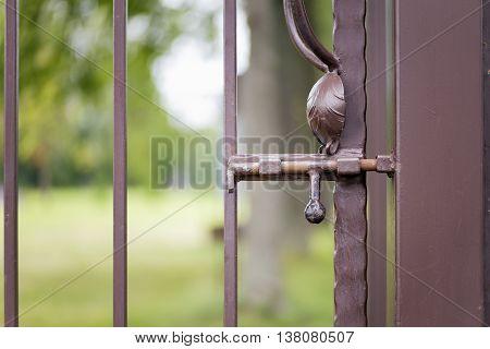 Rusty latch on a brown metallic gates