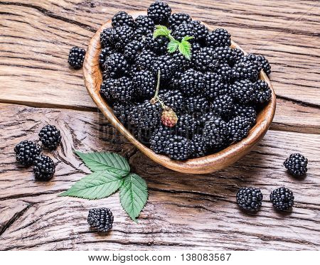 Blackberries in the wooden bowl on the table.