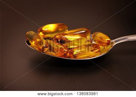 Fish oil in spoon with black background
