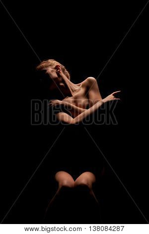 unrecognizable young blond woman posing in dark