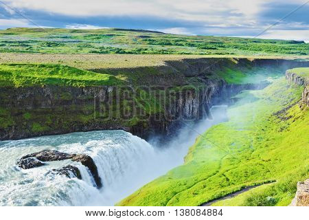 Grandiose Gullfoss in Iceland. In July raging water is lit with the bright morning sun. River banks grew with a green northern moss