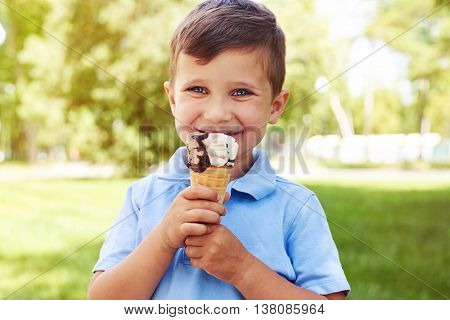 Small boy with beautiful blue eyes is holding an ice-cream in the park on a  sunny summer day