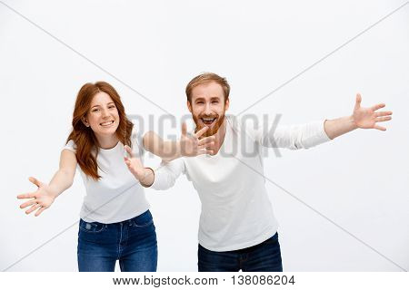 Happy redhead girl and boy standing over white background smiling