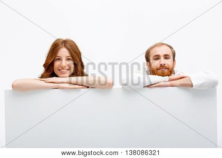 Funny redhead boy and girl hiding at white table smiling