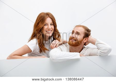 Funny redhead boy and girl posing at white table smiling