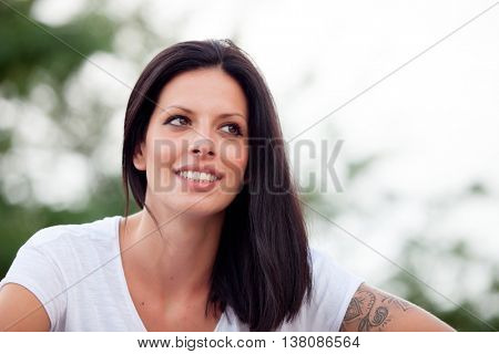 Young beautiful woman with brunette hair and perfect smile  posing in park