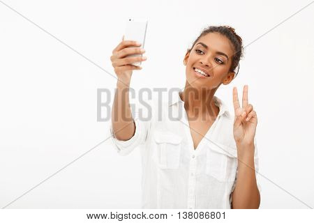 Portrait of young beautiful african girl in white blouse making selfie, smiling, showing peace over white background.