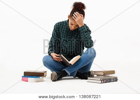 Portrait of upset young beautiful african girl in green blouse and jeans sitting on floor, reading book over white background. Copy space.