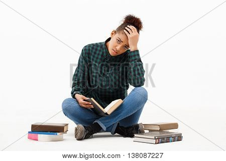 Portrait of upset young beautiful african girl in green blouse and jeans looking at camera, sitting on floor with books over white background. Copy space.