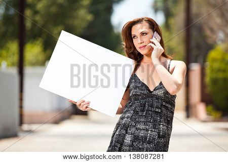 Transgender female on cell phone with blank poster board sign.