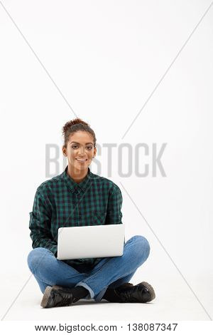 Portrait of young beautiful african girl with laptop smiling, looking at camera over white background. Copy space.