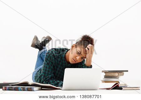 Portrait of upset young beautiful african girl with laptop and books thinking, looking at camera over white background. Copy space.