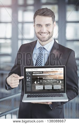 Composite image of website interface against happy businessman showing laptop