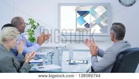 Business team applauding and looking at white screen against smartphone with graphic background