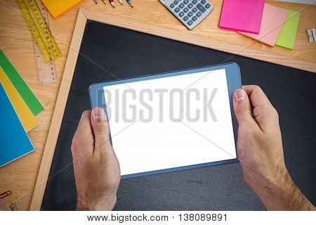 Chalkboard on desk against cropped image of person holding tablet