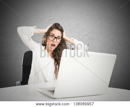 Businesswoman with a stunned expression and stressed front of the laptop
