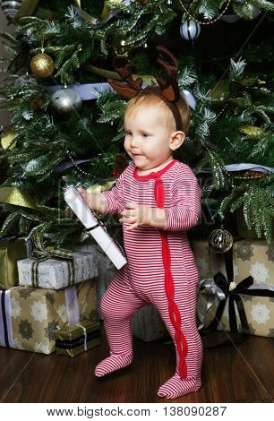 Little baby girl with the gift box near  Decorating Christmas tr